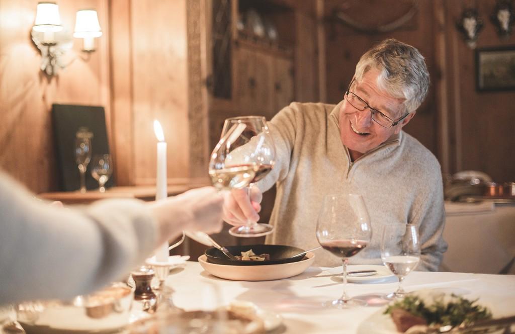 chalet-lech-luxuschalet-am-arlberg-lech-lodge-luxusferienwohnung-abendessen-wein-anstossen-speisen